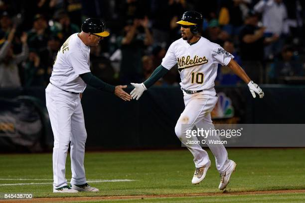 Marcus Semien of the Oakland Athletics is congratulated by acting third base coach Steve Scarsone after hitting a grand slam home run against the...