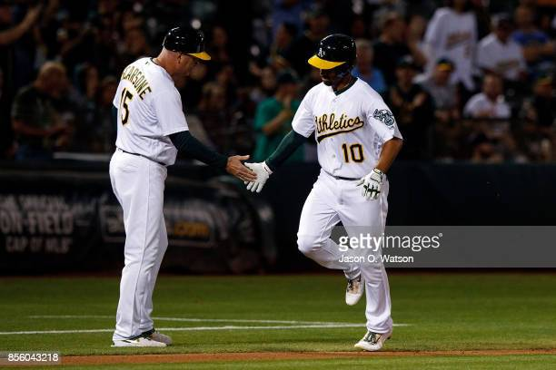 Marcus Semien of the Oakland Athletics is congratulated by acting third base coach Steve Scarsone after hitting a home run against the Seattle...