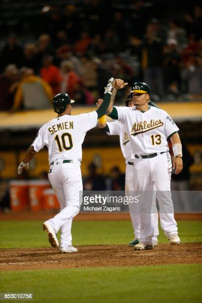 Marcus Semien of the Oakland Athletics is congratulated by Bruce Maxwell after hitting a home run during the game against the Houston Astros at the...