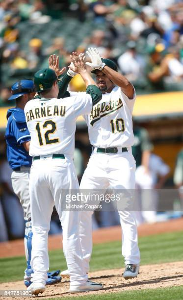 Marcus Semien of the Oakland Athletics is congratulated by Dustin Garneau after hitting a home run during the game against the Kansas City Royals at...
