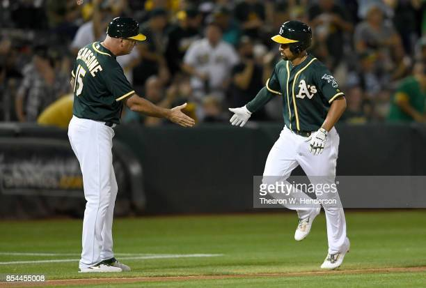 Marcus Semien of the Oakland Athletics is congratulated by third base coach Steve Scarsone after Semien hit a lead off home run against the Seattle...
