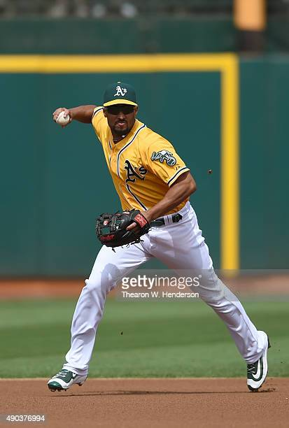 Marcus Semien of the Oakland Athletics makes an off balance throw to first base but not in time to get Kelby Tomlinson of the San Francisco Giants...