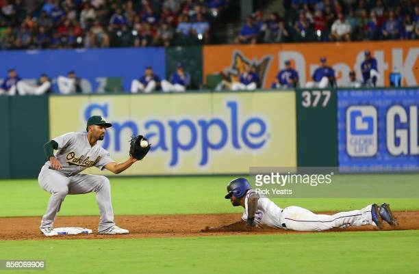 Marcus Semien of the Oakland Athletics misses the tag on Delino DeShields of the Texas Rangers stealing second base in the second inning at Globe...