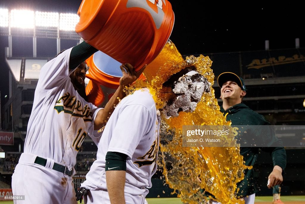 Marcus Semien #10 of the Oakland Athletics pours Gatorade on Jed Lowrie #8 after he hit a walk off single during the ninth inning against the Houston Astros at the Oakland Coliseum on September 8, 2017 in Oakland, California. The Oakland Athletics defeated the Houston Astros 9-8.