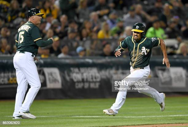 Marcus Semien of the Oakland Athletics racing past third base coach Steve Scarsone scores against the Texas Rangers in the bottom of the fifth inning...