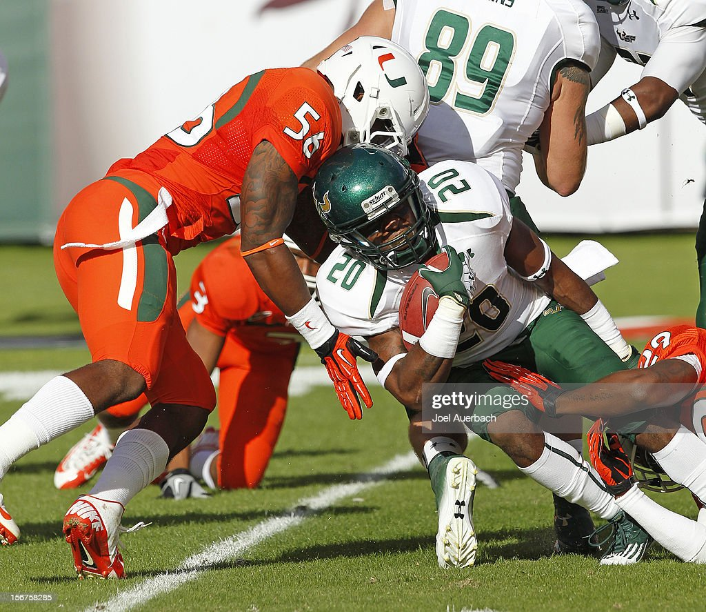 Marcus Shaw #20 of the South Florida Bulls is tackled by Rayshawn Jenkins #29 and Raphael Kirby #56 of the Miami Hurricanes during the opening kickoff on November 17, 2012 at Sun Life Stadium in Miami Gardens, Florida. The Hurricanes defeated the Bulls 40-9.