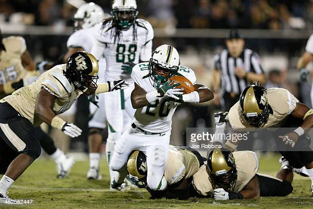 Marcus Shaw of the South Florida Bulls jis tackled against the Central Florida Knights during the first half of the game at Bright House Networks...