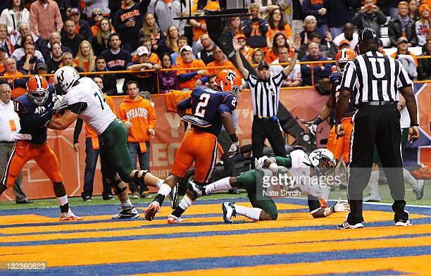 Marcus Shaw of the South Florida Bulls scores a touchdown as he is chased by Syracuse Orange player Olando Fisher during the game at the Carrier Dome...