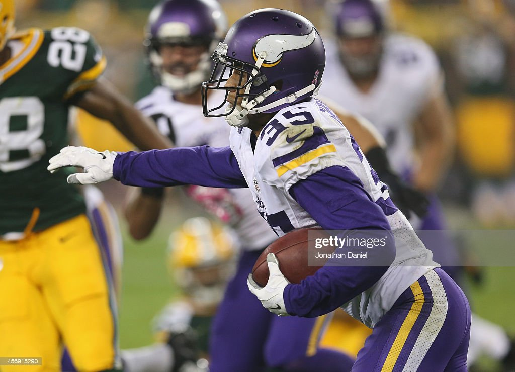 Marcus Sherels of the Minnesota Vikings carries the football against the Green Bay Packers in the second half at Lambeau Field on October 2 2014 in...