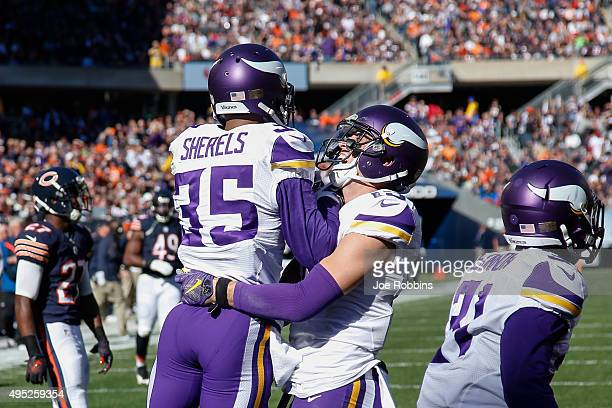 Marcus Sherels of the Minnesota Vikings celebrates with Adam Thielen after scoring a touchdown on a 65 yard punt return against the Chicago Bears in...