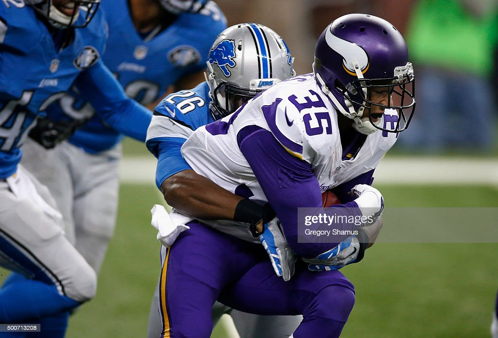 Marcus Sherels of the Minnesota Vikings return a second quarter punt and tries to break the tackle by Don Carey of the Detroit Lions at Ford Field on...