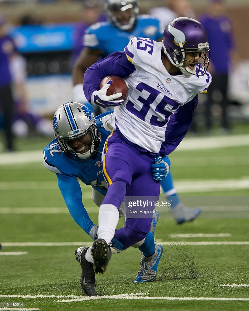 Marcus Sherels of the Minnesota Vikings runs past the diving Isa AbdulQuddus of the Detroit Lions during an NFL game at Ford Field on October 25 2015...