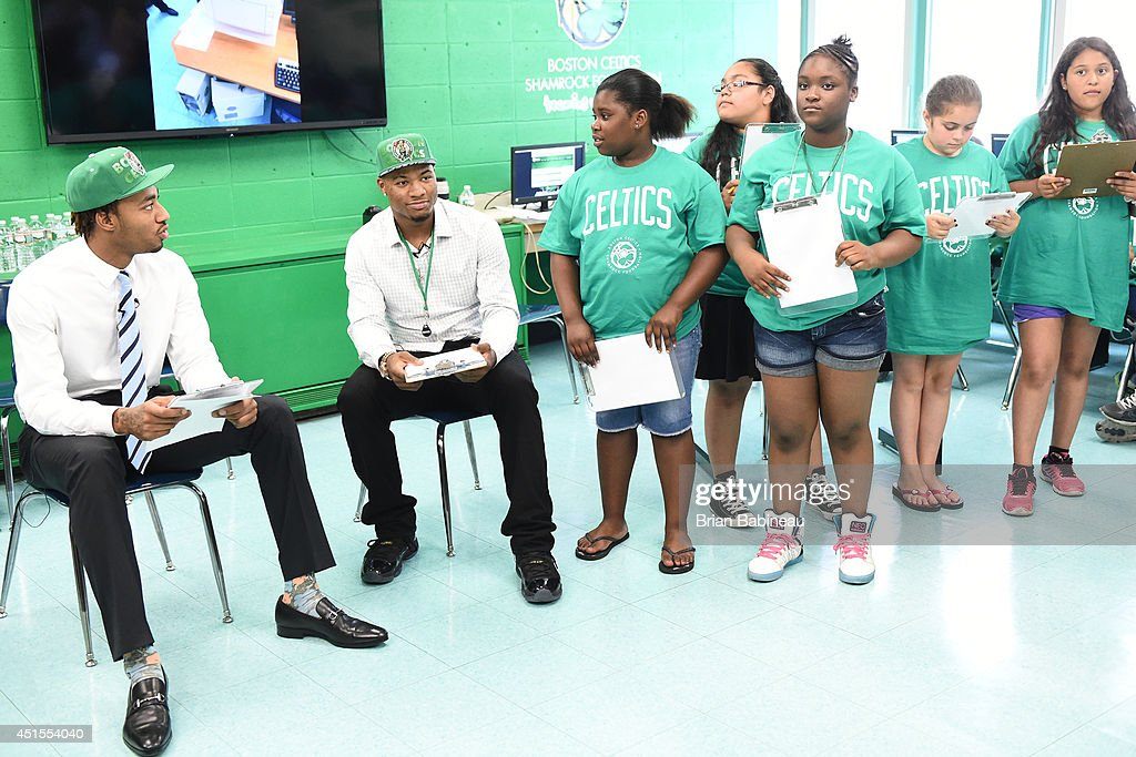 Marcus Smart and James Young of the Boston Celtics help unveil a renovated technology lab on June 30, 2014 at Harvard Kent Elementary School in Charlestown, Massachusetts .