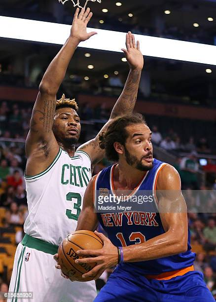 Marcus Smart of the Boston Celtics defends Joakim Noah of the New York Knicks during the first quarter at TD Garden on October 17 2016 in Boston...