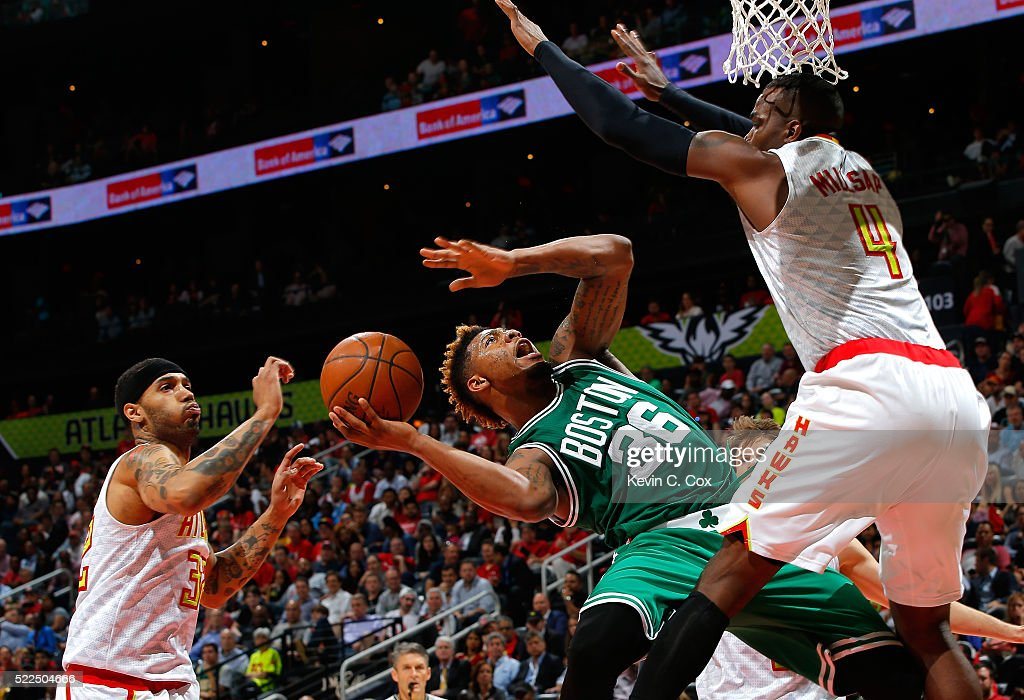 Marcus Smart of the Boston Celtics drives against Paul Millsap and Mike Scott of the Atlanta Hawks in Game Two of the Eastern Conference...