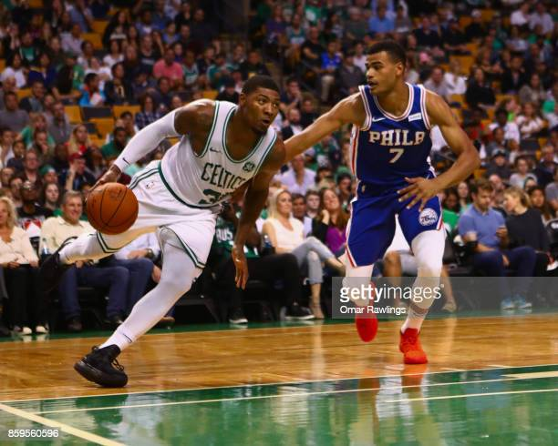 Marcus Smart of the Boston Celtics drives on Timothe LuwawuCabarrot of the Philadelphia 76ers during the first half of the game at TD Garden on...