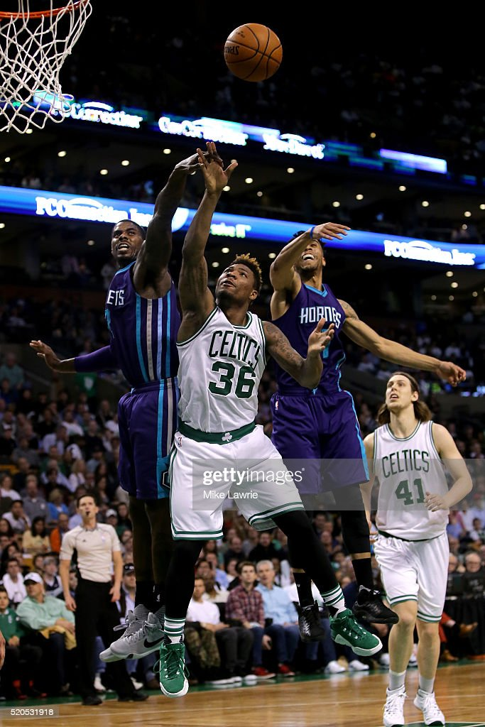 Marcus Smart of the Boston Celtics goes up with the ball against Marvin Williams and Courtney Lee of the Charlotte Hornets in the third quarter at TD...