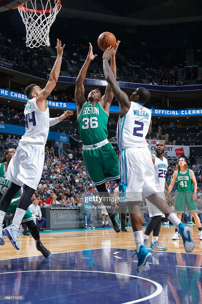 Marcus Smart of the Boston Celtics shoots against Jeff Taylor and Marvin Williams of the Charlotte Hornets at Time Warner Cable Arena on March 30...