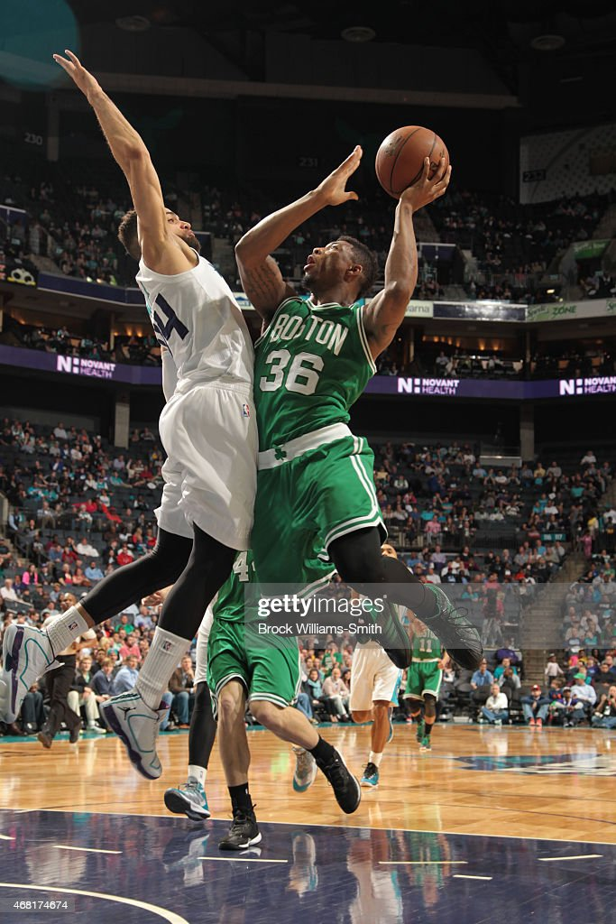 Marcus Smart of the Boston Celtics shoots against Jeff Taylor of the Charlotte Hornets during the game at the Time Warner Cable Arena on March 30...