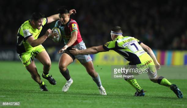 Marcus Smith of Harlequins breaks with the ball past Marc Jones and Ben Curry during the Aviva Premiership match between Harlequins and Sale Sharks...