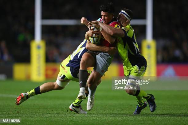 Marcus Smith of Harlequins is tackled by Ben Curry and Bryn Evans of Sale Sharks during the Aviva Premiership match between Harlequins and Sale...
