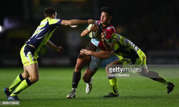 Marcus Smith of Harlequins is tackled by Ross Harrison and AJ MacGinty of Sale Sharks during the Aviva Premiership match between Harlequins and Sale...