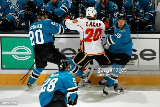 Marcus Sorensen and Micheal Haley of the San Jose Sharks battle along the boards with Curtis Lazar of the Calgary Flames at SAP Center at San Jose on...
