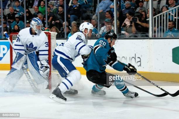 Marcus Sorensen of the San Jose Sharks skates against Roman Polak of the Toronto Maple Leafs as Frederik Andersen of the Toronto Maple Leafs looks on...