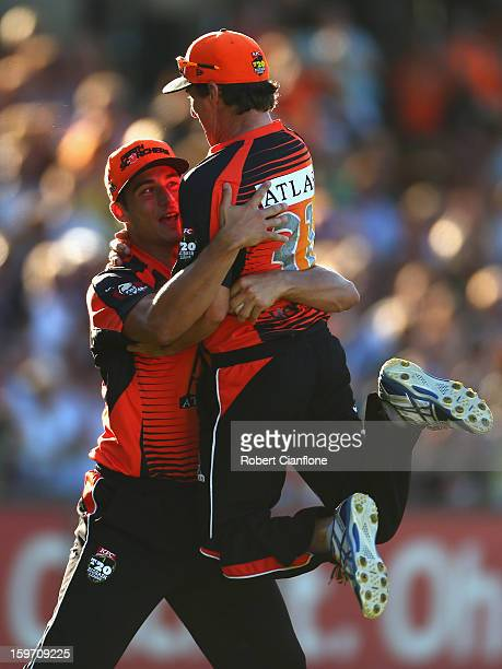 Marcus Stoinis of the Scorchers celebrates with Brad Hogg after taking a catch to dismiss Luke Pomersbach of the Heat during the Big Bash League...