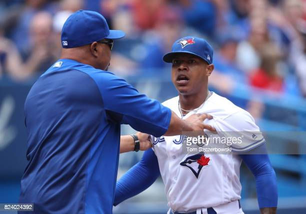 Marcus Stroman of the Toronto Blue Jays argues as he is restrained by bench coach DeMarlo Hale after being ejected in the fifth inning during MLB...