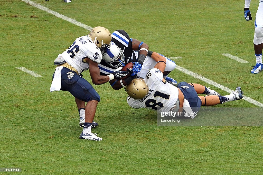 Marcus Thomas #26 and Brendan Dudeck #81 of the Navy Midshipmen tackle DeVon Edwards #27 of the Duke Blue Devils at Wallace Wade Stadium on October 12, 2013 in Durham, North Carolina. Duke defeated Navy 35-7.