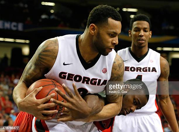 Marcus Thornton of the Georgia Bulldogs grabs a rebound against Demarco Cox of the Mississippi Rebels during the quarterfinals of the SEC Men's...