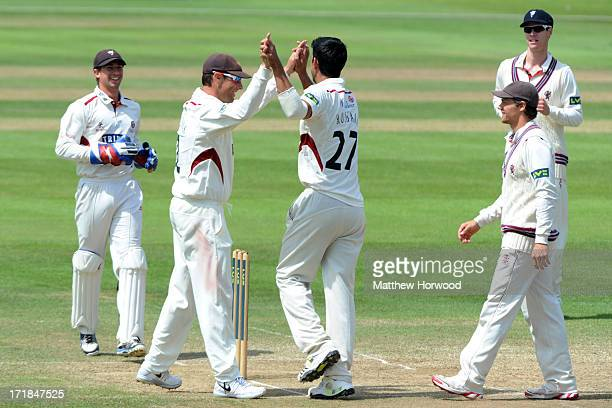 Marcus Trescothick of Somerset celebrates the wicket of Australia's Ed Cowan with teammate Gemaal Hussain during day four of the Somerset versus...