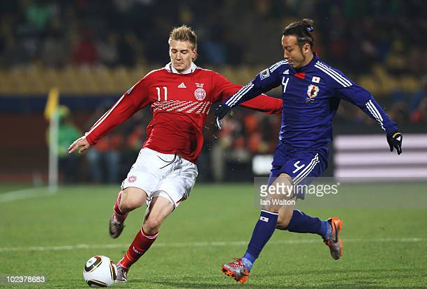 Marcus Tulio Tanaka of Japan challenges Nicklas Bendtner of Denmark during the 2010 FIFA World Cup South Africa Group E match between Denmark and...