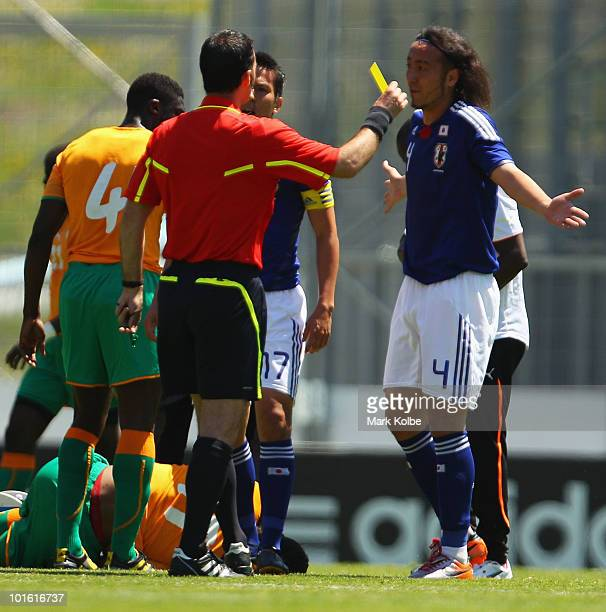 Marcus Tulio Tanaka of Japan is given a yellow card after a tackle on Didier Drogba of the Ivory Coast during the Japan v Ivory Coast International...
