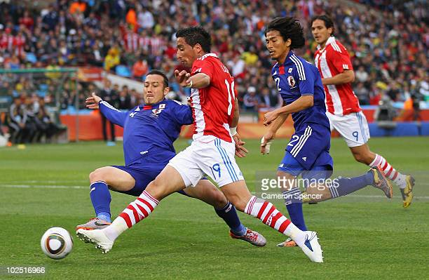 Marcus Tulio Tanaka of Japan tackles Lucas Barrios of Paraguay during the 2010 FIFA World Cup South Africa Round of Sixteen match between Paraguay...