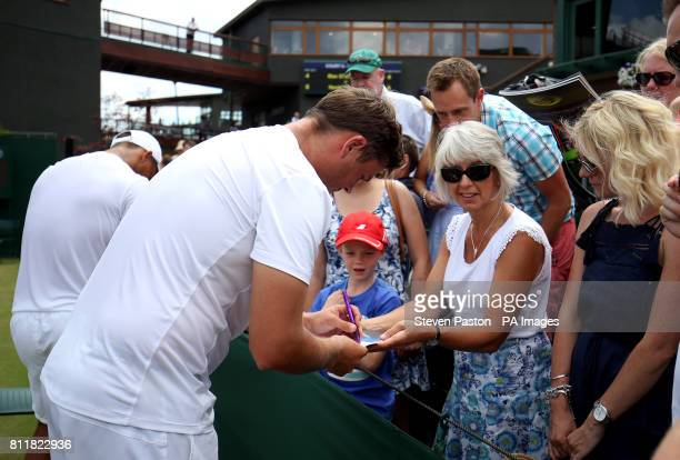 Marcus Willis signs autographs for fans after his doubles match with Jay Clarke on day seven of the Wimbledon Championships at The All England Lawn...
