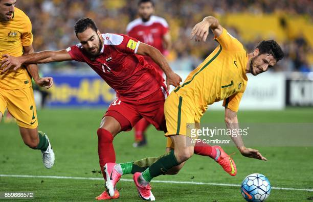 Mardek Mardkian of Syria tackles Mathew Leckie of Australia during their 2018 World Cup football qualifying match played in Sydney on October 10 2017...