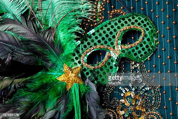 Mardi Gras mask on beaded green background.
