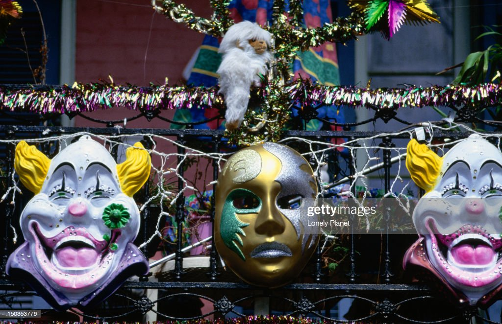 Mardi Gras masks hanging from a French Quarter balcony in New Orleans. : Stock Photo