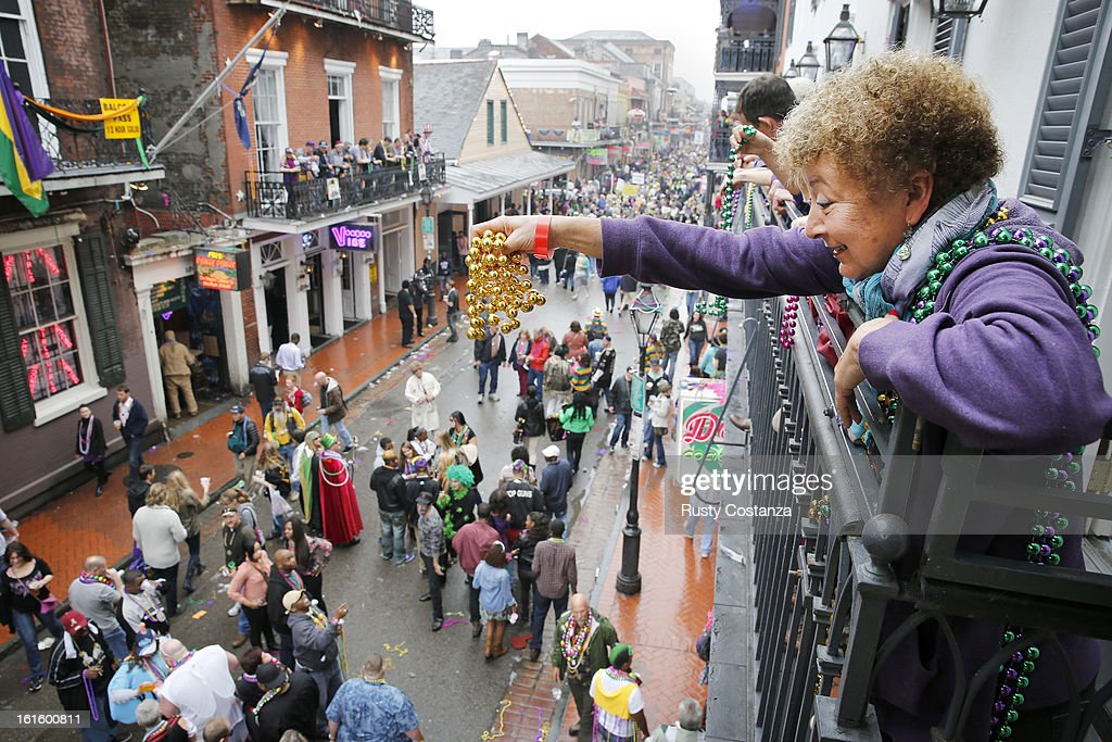 Mardi Gras reveler dangles a pair of beads off of a balcony on Bourbon Street in New Orleans on Mardi Gras Day Fat Tuesday the traditional...