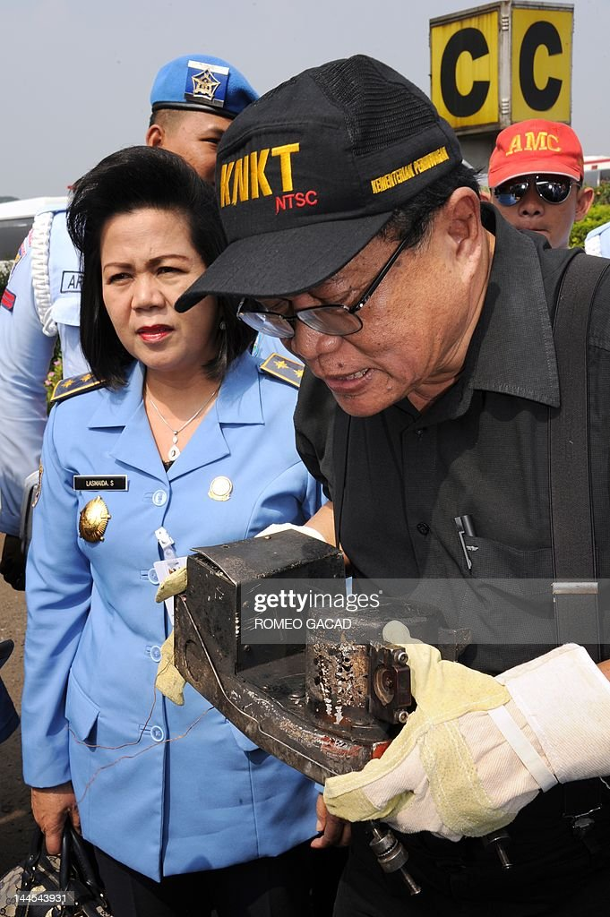 Mardjono Siswosuwarno head of the Indonesian investigating panel inspects the recovered partly charred cockpit voice recorder of the Russian Sukhoi...