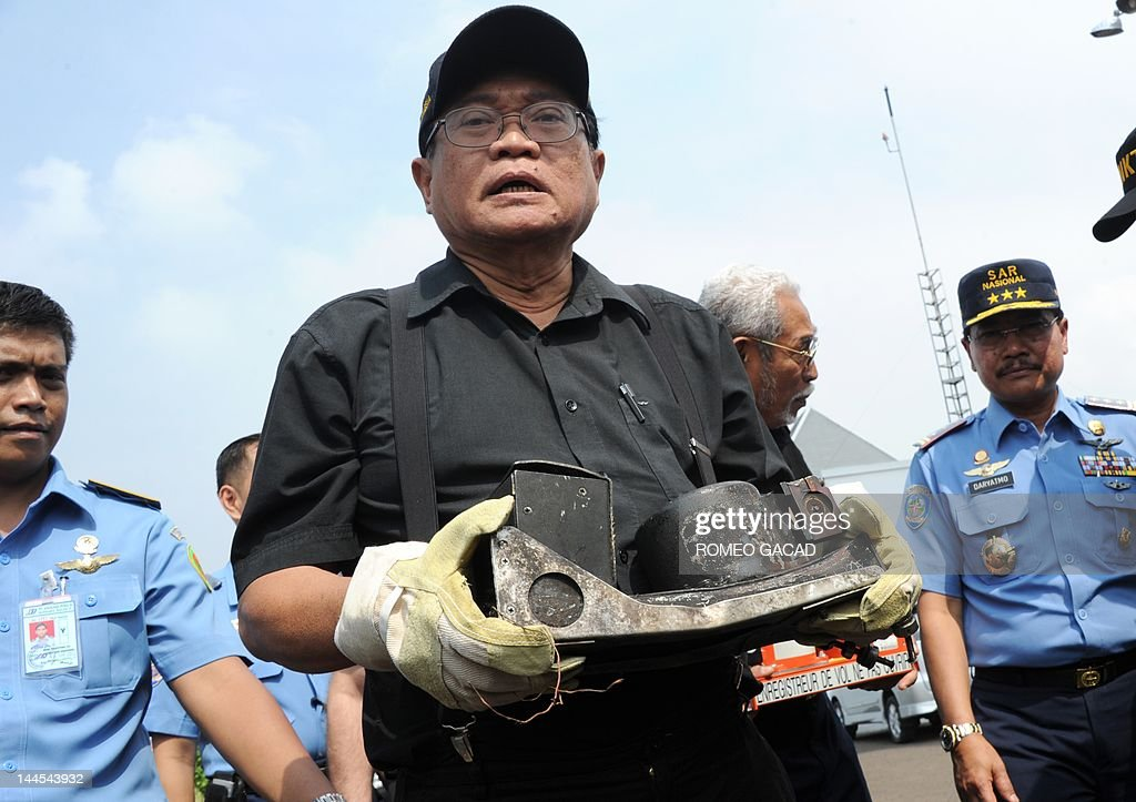 Mardjono Siswosuwarno head of the Indonesian investigating panel holds the recovered partly charred cockpit voice recorder of the Russian Sukhoi...