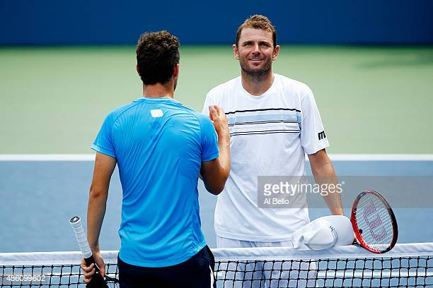 Mardy Fish of the United States shakes hands with Marco Cecchinato of Italy after their Men's Singles First Round match on Day One of the 2015 US...