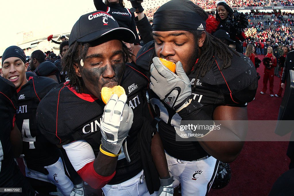 Mardy Gilyard and Ricardo Mathews of the Cincinnati Bearcats bite into oranges after the game against the Syracuse Orange at Nippert Stadium on...