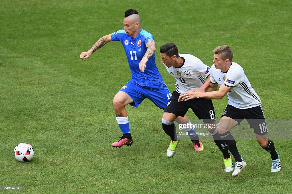 Marek Hamsik (L) of Slovakia competes for the ball against <a gi-track='captionPersonalityLinkClicked' href=/galleries/search?phrase=Mesut+Oezil&family=editorial&specificpeople=764075 ng-click='$event.stopPropagation()'>Mesut Oezil</a> (C) and <a gi-track='captionPersonalityLinkClicked' href=/galleries/search?phrase=Toni+Kroos&family=editorial&specificpeople=638597 ng-click='$event.stopPropagation()'>Toni Kroos</a> (R) of Germany during the UEFA EURO 2016 round of 16 match between Germany and Slovakia at Stade Pierre-Mauroy on June 26, 2016 in Lille, France.