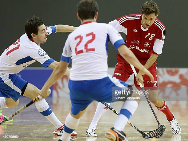 Marek Vavra of Czech Republic vies for the ball with Suter Simon of Switzerland during the World University Championship Floorball match between...