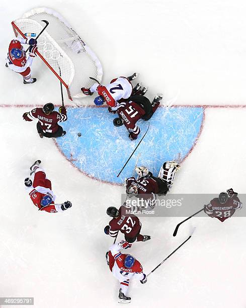 Marek Zidlicky of Czech Republic scores while being hit into the net by Martins Karsums of Latvia as Edgars Masalskis looks on in the second period...