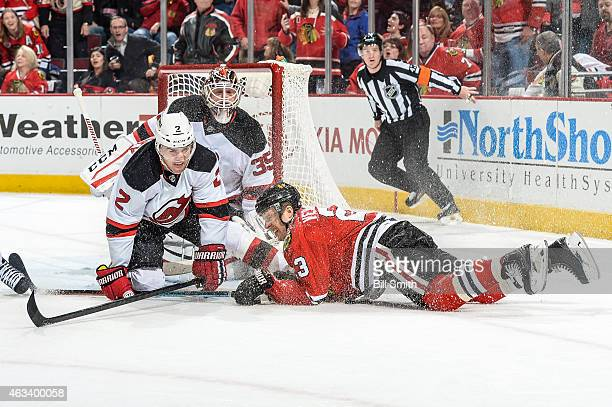 Marek Zidlicky of the New Jersey Devils and Kris Versteeg of the Chicago Blackhawks collide in front of goalie Cory Schneider during the NHL game at...