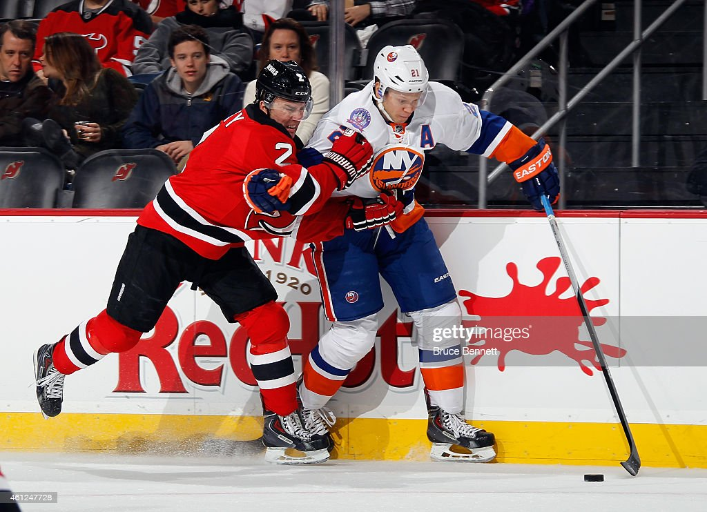 Marek Zidlicky of the New Jersey Devils hangs on to Kyle Okposo of the New York Islanders during the first period at the Prudential Center on January...